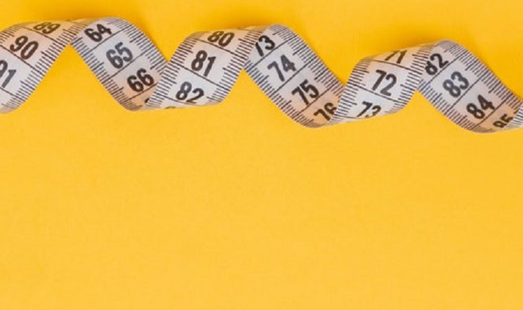 A twisted tape measure on a yellow background