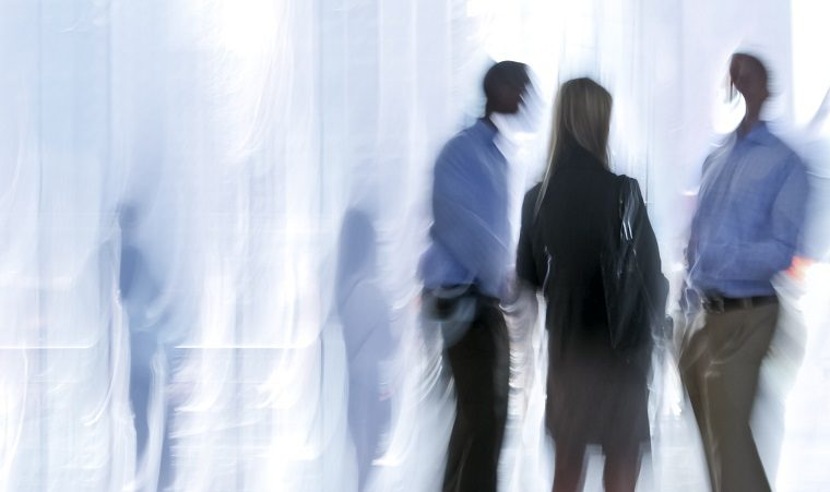 Blurred image of three business professionals talking with other silhouettes in the background