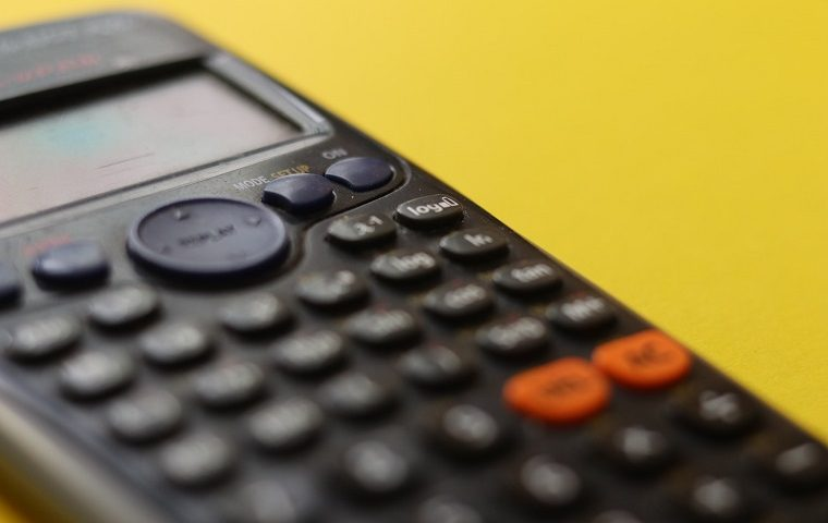 Close up image of a calculator on a yellow background
