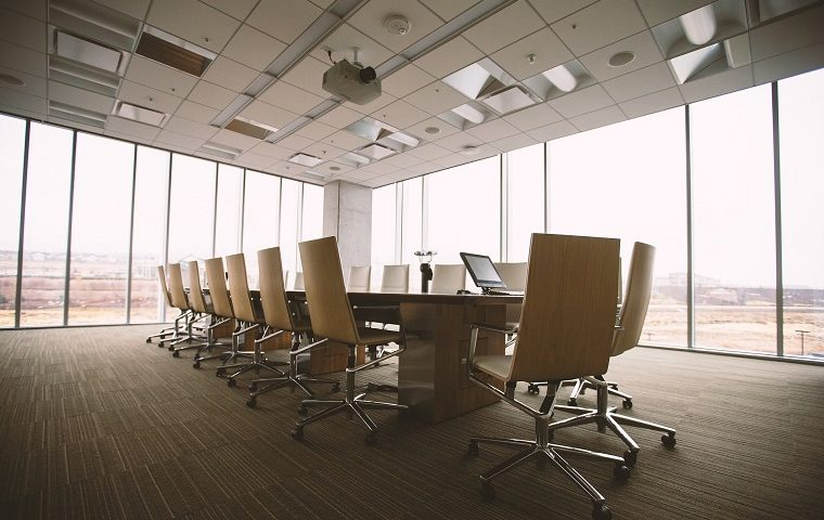 Empty chairs around a long conference board room