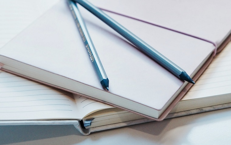 An open, empty notebook with two pencils balanced on top