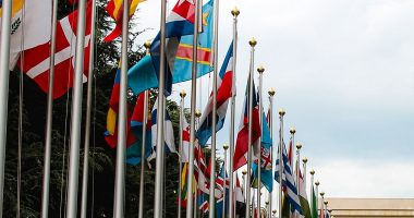 Rows of flags from different countries leading into the corner of a United Nations building