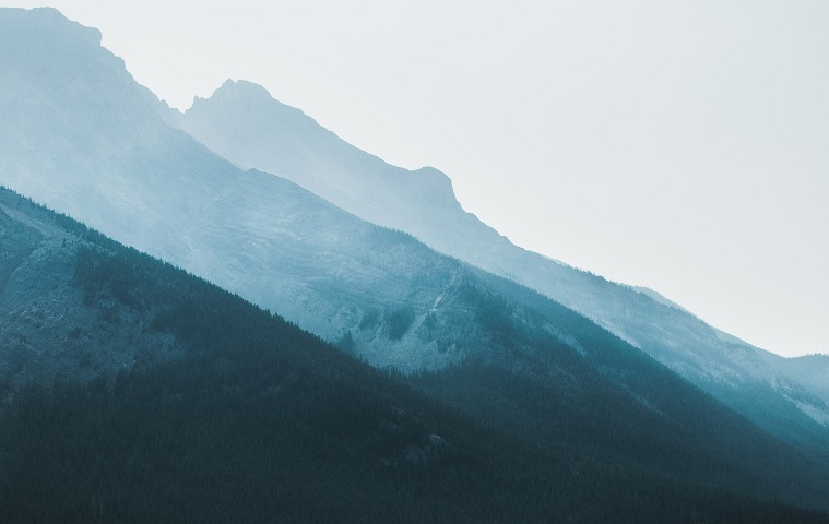 Hazy image of three different hills, getting higher towards the back of the image