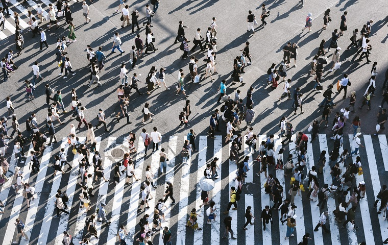A busy zebra crossing pictured from above, filled with people