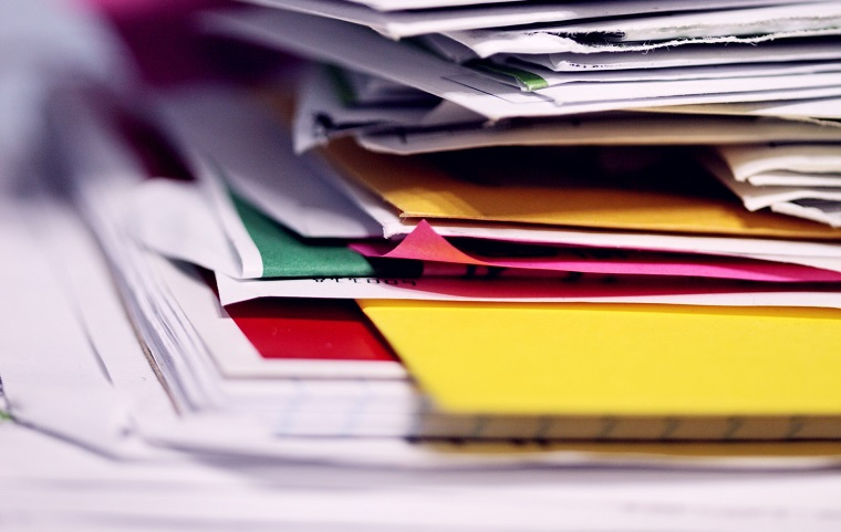 Close up stack of coloured and plain papers