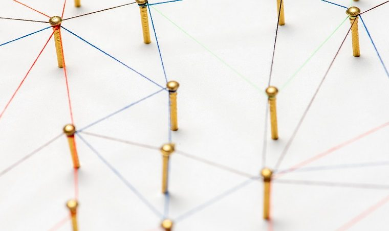 White background with gold pins at various intervals, joined together in different ways by a network of coloured strings