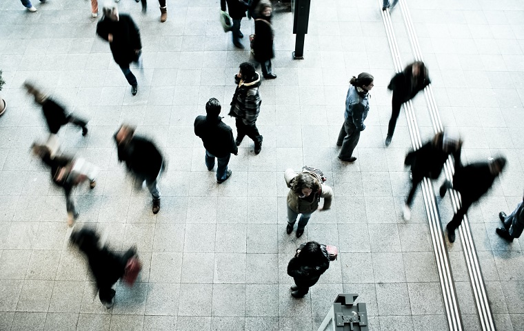 Blurred silhouettes of people in a public area, photographed from above