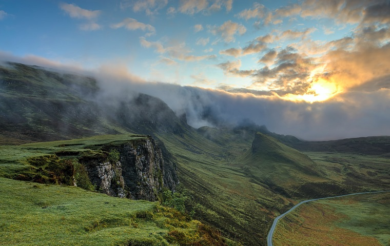 Green hills in front of a blur sky with dramatic grey clouds on the horizon with yellow sun peeking through